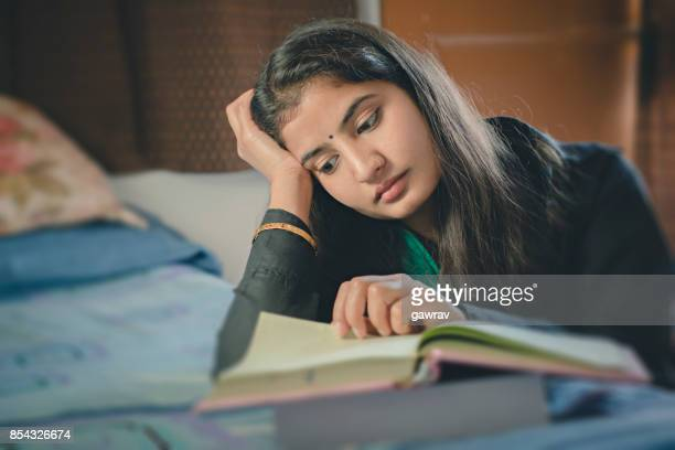 Education: Young woman studying book.