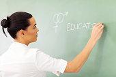 female high school educator writing sex education on chalkboard