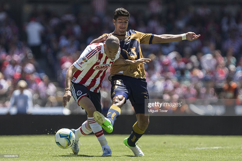 Eduerdo Herrera of Pumas fights for the ball with Jorge Enriquez of Chivas during a match between Pumas and Chivas as part of the Clausura 2013 at Olympic stadium on March 03, 2013 in Mexico City, Mexico.