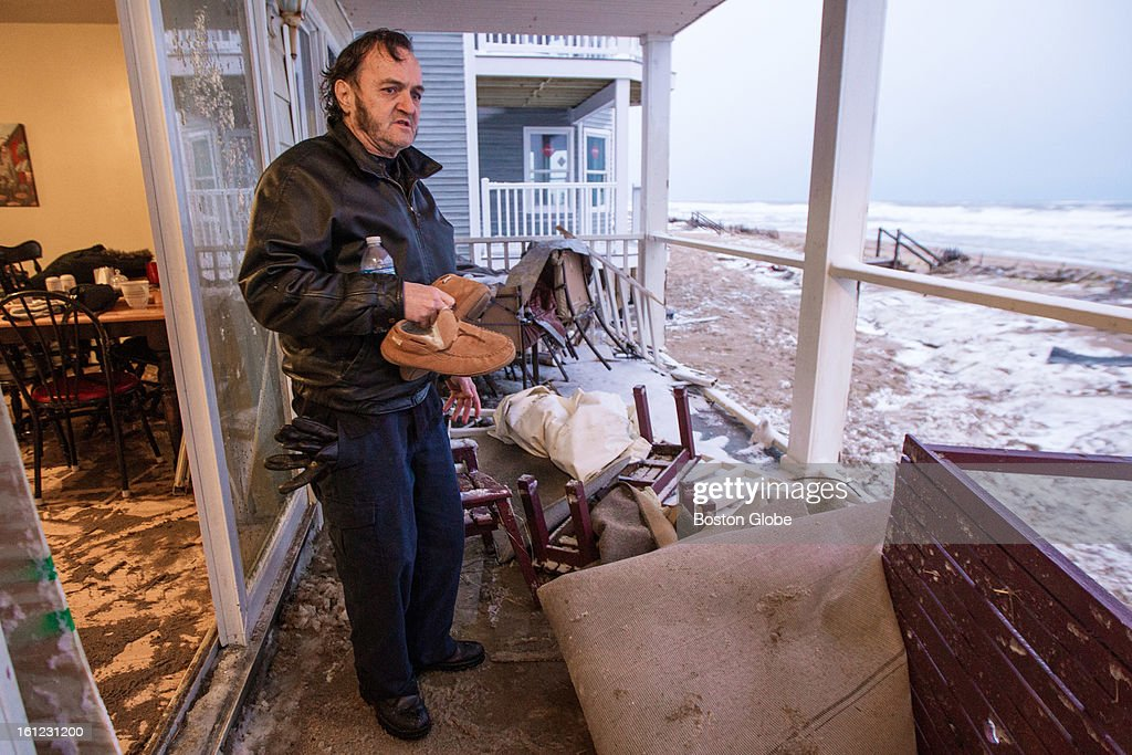 Edward Bemis inspects the damage to his home caused by a wave that crashed into their North End Boulevard home in Salisbury. Bemis was evacuated during the storm and has just returned home after a large winter storm hit the region and high surf damaged waterfront homes.