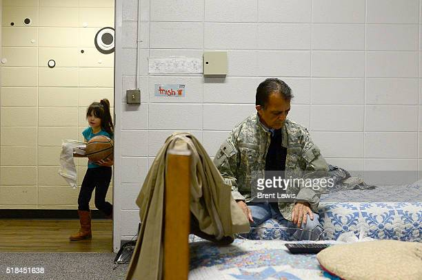 Edward Chavez sits on his bed before getting up to take out the trash while his daughter Ariana walks into their room at the Comitis Crisis Center on...