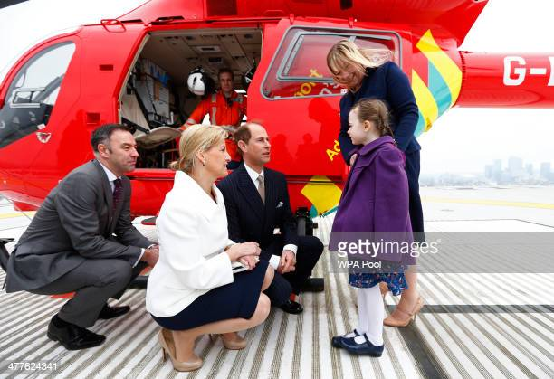 Edward Earl of Wessex his wife Sophie Countess of Wessex and the chief executive of London's Air Ambulance Graham Hodgkin crouch as they speak to...