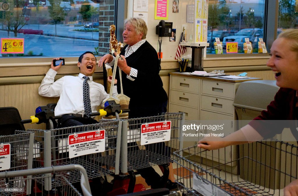 Edward Foye, a grocery clerk at the Market Basket in Biddeford, laughs as Joanne Twomey, former mayor of Biddeford, ran into the store around 7:15 p.m. Friday night, August 22, 2014, to celebrate the indications that Arthur T. Demoulas was going to buy the company. At right is employee Jackie Murphy. Nothing would be made official until the board met to discuss the bids that were made.