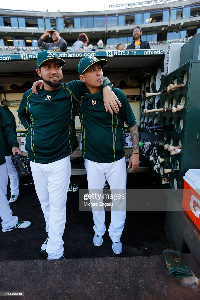 Edward Mujica and Jesse Chavez of the Oakland Athletics stand in the dugout prior to the game against the Los Angeles Angels of Anaheim at Oco...