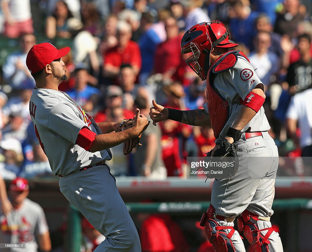 Edward Mujica #44 (L) and Yadier Molina #4 of the St. Louis Cardinals celebrate a win against the Chicago Cubs at Wrigley Field on May 8, 2013 in Chicago, Illinois. The Cardinals defeated the Cubs 5-4.