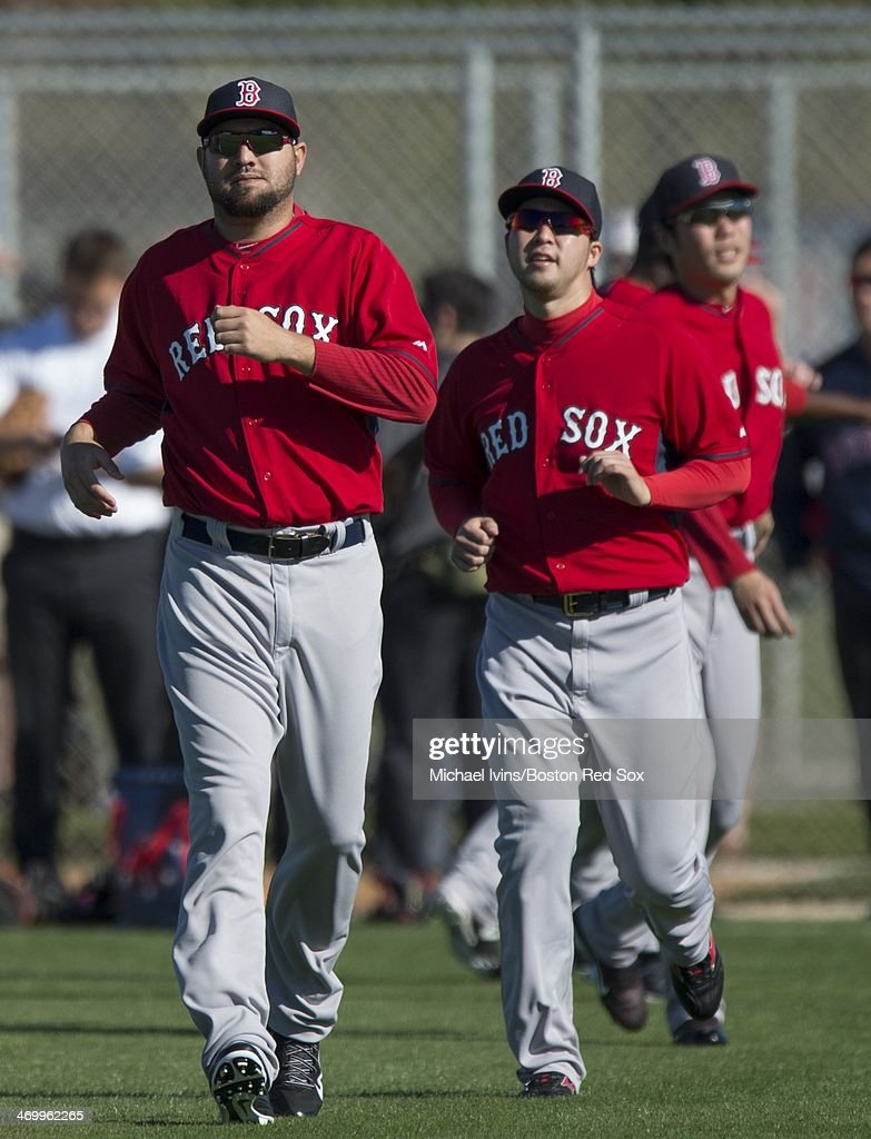 Edward Mujica of the Boston Red Sox runs in front of Junichi Tazawa during a Spring Training workout at Fenway South on February 17 2014 in Fort...