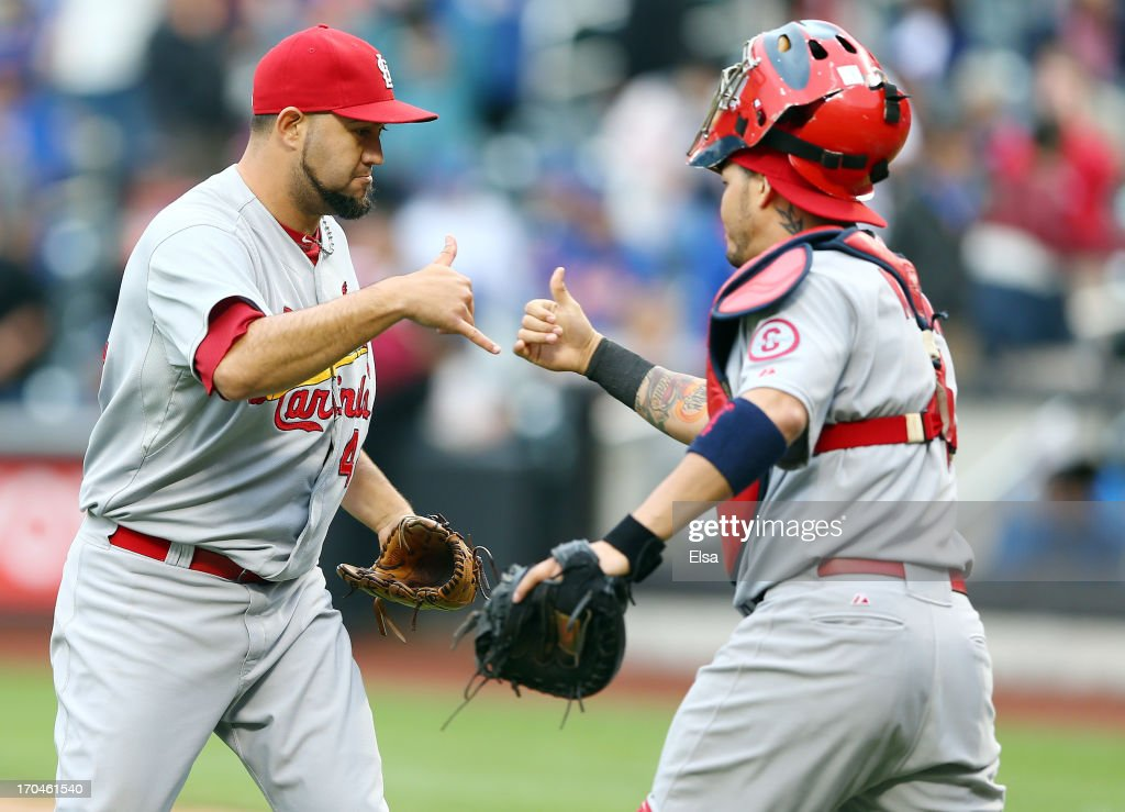 Edward Mujica of the St Louis Cardinals celebrates the win with teammate Yadier Molina#4 after the game against the New York Mets on June 13 2013 at...