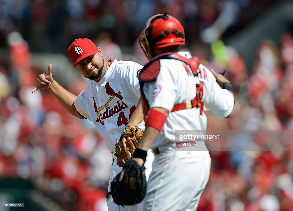 Edward Mujica of the St Louis Cardinals celebrates with Yadier Molina after closing out the ninth inning against the Cincinnati Reds at Busch Stadium...