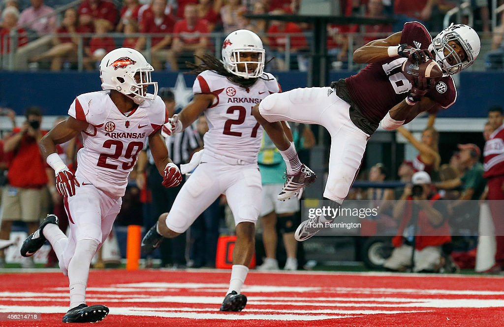 Edward Pope #18 of the Texas A&M Aggies pulls in a pass for a touchdown against Jared Collins #29 of the Arkansas Razorbacks and Alan Turner #27 of the Arkansas Razorbacks in the first half of the Southwest Classic at AT&T Stadium on September 27, 2014 in Arlington, Texas.