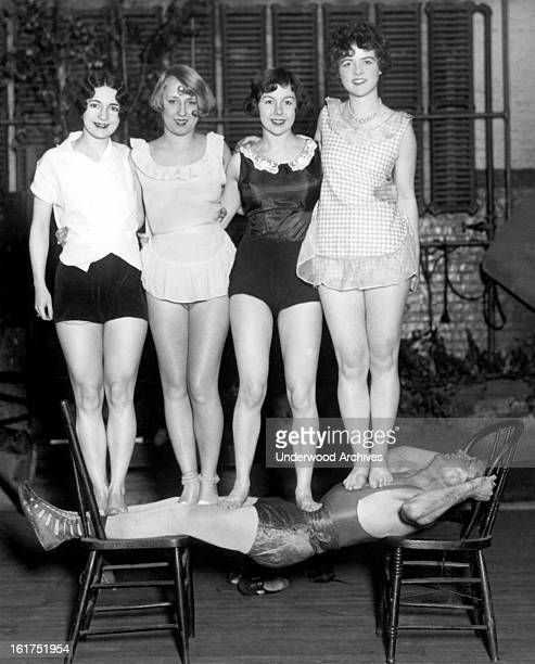 Edward Reece famous strongman shows his strength by supporting a troupe of four actresses while he is suspended between two chairs New York New York...