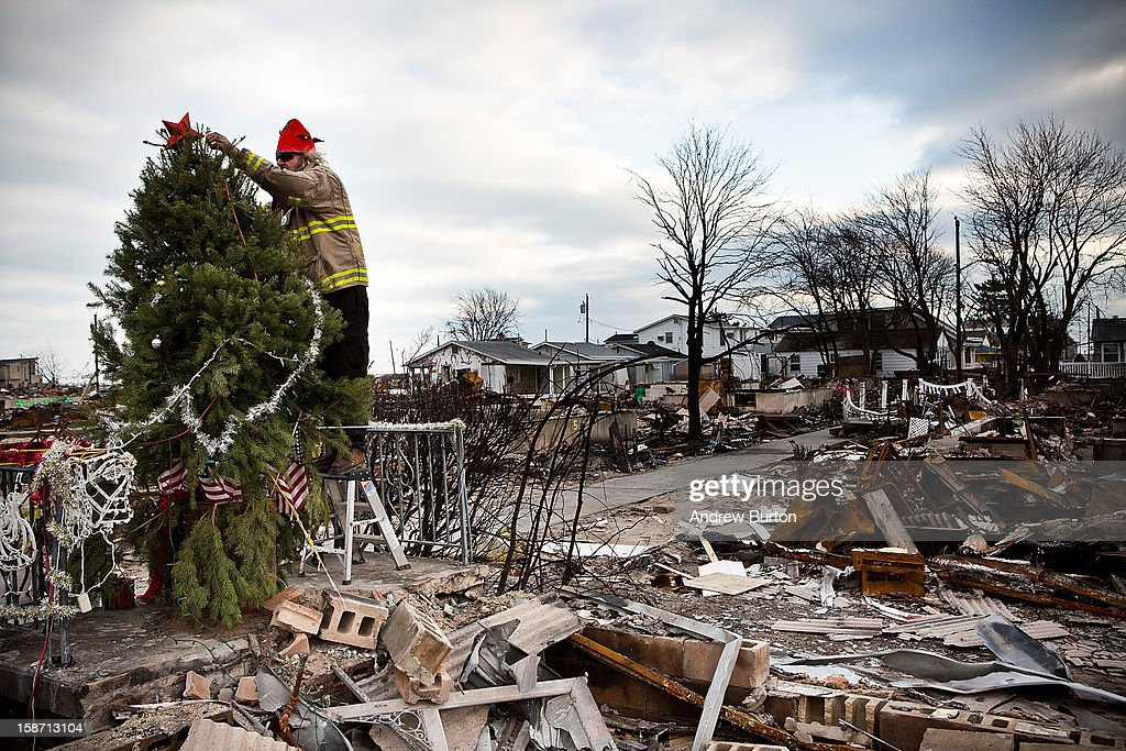 Edward ''Roaddawg'' Manley, a volunteer and honorary firefighter with the Point Breeze Volunteer Fire Department, places a star on top of a Christmas Tree in the Breezy Point neighborhood of the Borough of Queens on December 25, 2012 in New York City.