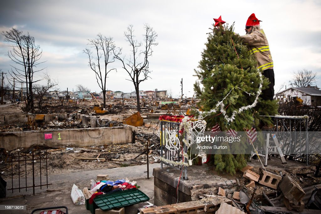 Edward 'Roaddawg' Manley, a volunteer and honory firefighter with the Point Breeze Volunteer Fire Department, places a star on top of a Christmas Tree December 25, 2012 in the Breezy Point neighborhood of the Queens borough of New York City. Residents are still struggling to recover from a massive fire that destroyed over 100 homes during Superstorm Sandy.