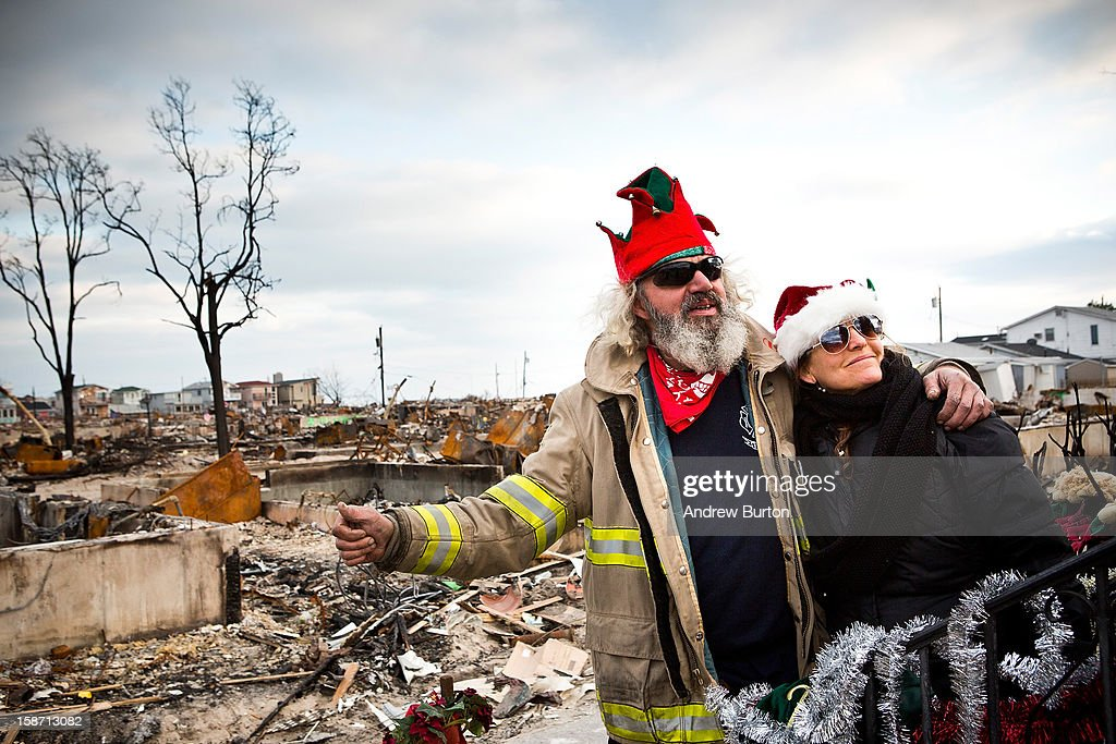 Edward 'Roaddawg' Manley, a volunteer and honory firefighter with the Point Breeze Volunteer Fire Department, puts his arm around a volunteer who identified herself as 'Nancy,' after decorating a Christmas tree December 25, 2012 in the Breezy Point neighborhood of the Queens borough of New York City. Residents are still struggling to recover from a massive fire that destroyed over 100 homes during Superstorm Sandy.