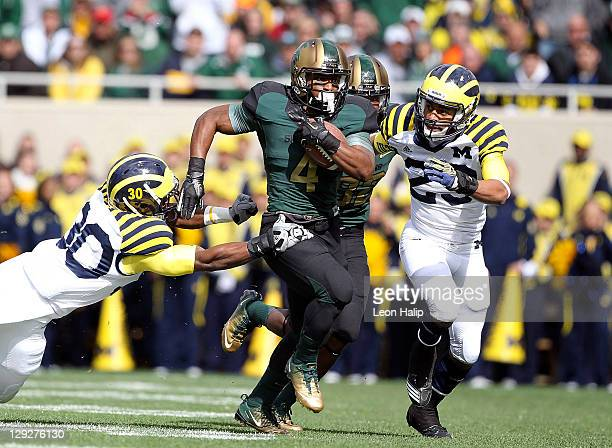Edwin Baker of the Michigan State Spartans runs for a first down in the second quarter as Thomas Gordon and Troy Woolfolk attempt to make the stop...