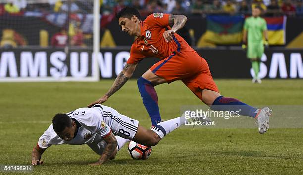 Edwin Cardona of Colombia and Pablo Hernandez of Chile fall during a Semifinal match between Colombia and Chile at Soldier Field as part of Copa...