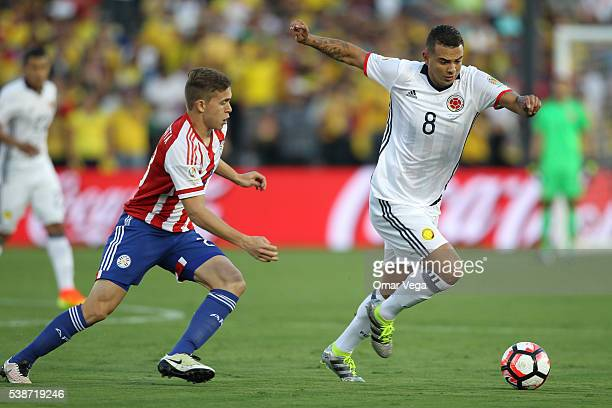 Edwin Cardona of Colombia fights for the ball with Robert Piris Da Motta of Paraguay during a group A match between Colombia and Paraguay at Rose...