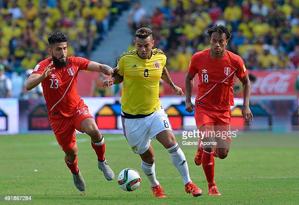 Edwin Cardona of Colombia struggles for the ball with Josepmir Ballon and Andre Carrillo of Peru during a match between Colombia and Peru as part of...