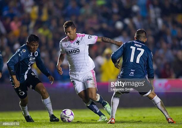 Edwin Cardona of Monterrey tries to dribble Dionicio Escalante and Mario Osuna of Querétaro during the 15th round match between Queretaro and...