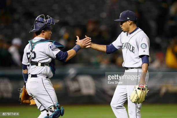 Edwin Diaz and Carlos Ruiz of the Seattle Mariners shake hands after they beat the Oakland Athletics at Oakland Alameda Coliseum on August 8 2017 in...