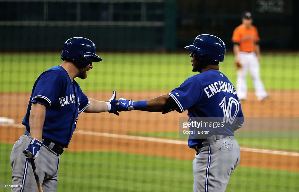 Edwin Encarnacion and Adam Lind #26 of the Toronto Blue Jays celebrate after Encarnacion hit a solo home run in the first inning against the Houston Astros at Minute Maid Park on August 23, 2013 in Houston, Texas.