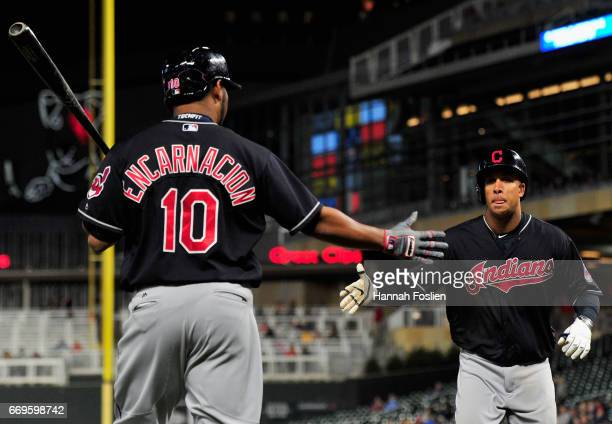 Edwin Encarnacion of the Cleveland Indians congratulates teammate Michael Brantley on hitting a solo home run against the Minnesota Twins during the...