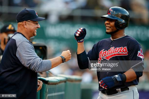 Edwin Encarnacion of the Cleveland Indians is congratulated by manager Terry Francona after scoring a run against the Oakland Athletics during the...