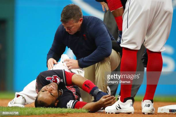 Edwin Encarnacion of the Cleveland Indians receives medical attention after an injury first inning against the New York Yankees during game two of...