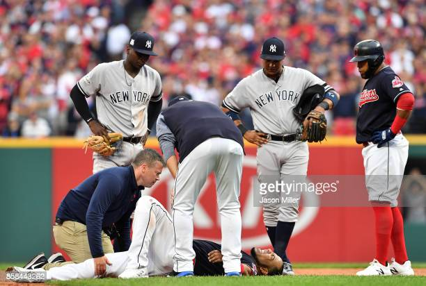 Edwin Encarnacion of the Cleveland Indians receives medical attention after an injury in the first inning against the New York Yankees during game...