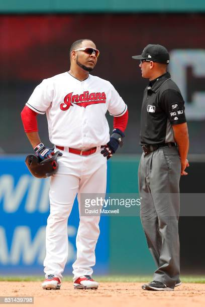 Edwin Encarnacion of the Cleveland Indians talks with second base umpire Roberto Ortiz during a pitching change against the Colorado Rockies in the...