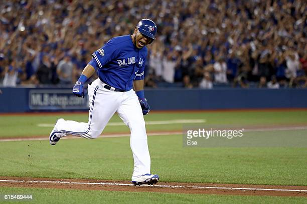 Edwin Encarnacion of the Toronto Blue Jays celebrates after hitting an RBI double scoring Ryan Goins and Jose Bautista in the seventh inning against...