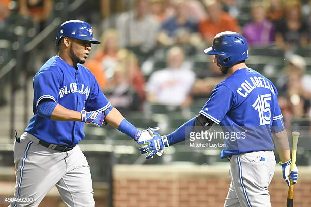 Edwin Encarnacion of the Toronto Blue Jays celebrates hitting a solo home run with Chris Colabello in the second inning during a baseball game...