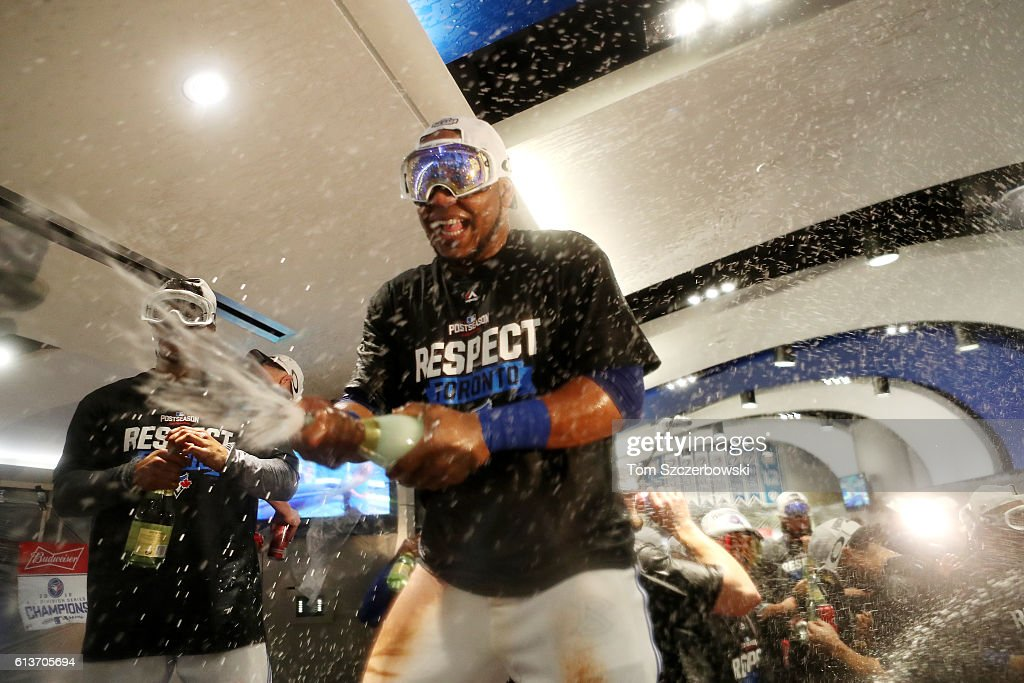 Edwin Encarnacion #10 of the Toronto Blue Jays celebrates in the clubhouse after the Toronto Blue Jays defeated the Texas Rangers 7-6 for game three of the American League Division Series at Rogers Centre on October 9, 2016 in Toronto, Canada.