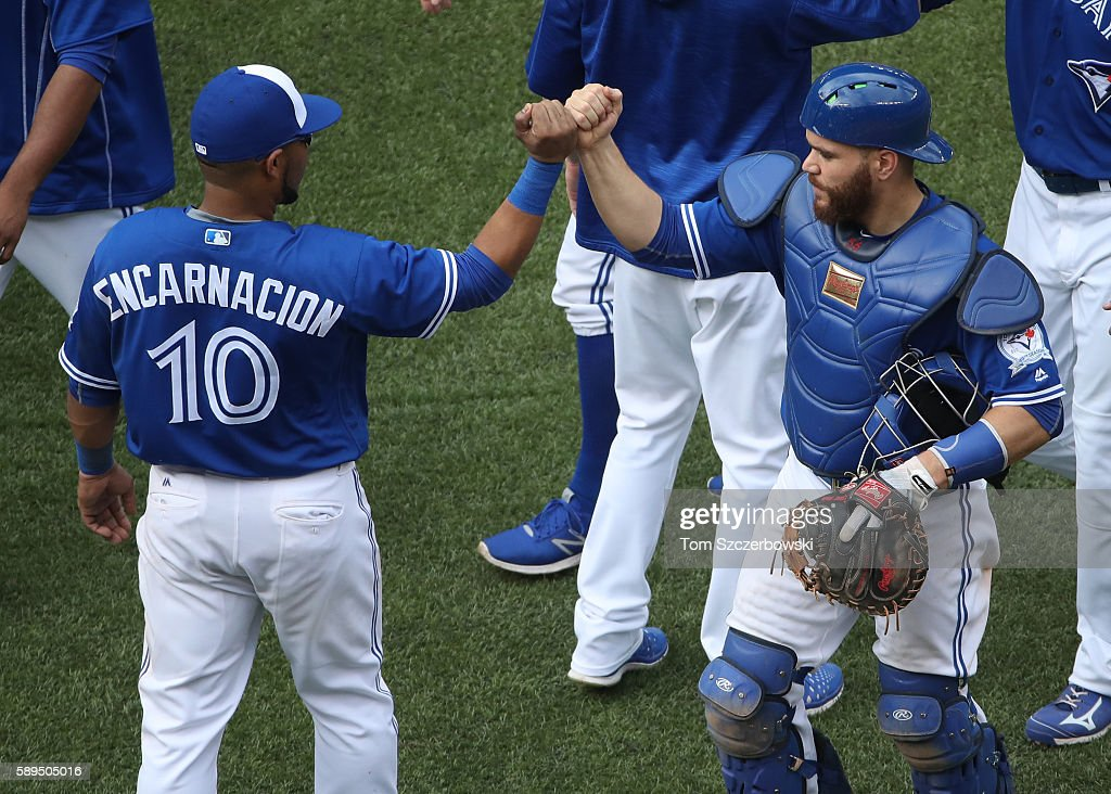 Edwin Encarnacion #10 of the Toronto Blue Jays celebrates their victory with Russell Martin #55 during MLB game action against the Houston Astros on August 14, 2016 at Rogers Centre in Toronto, Ontario, Canada.