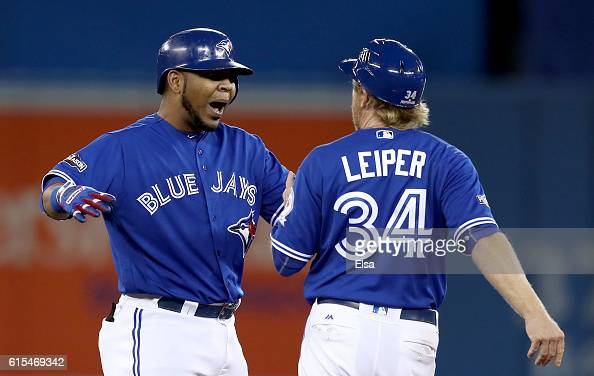 Edwin Encarnacion of the Toronto Blue Jays celebrates with first base coach Tim Leiper after an RBI double scoring Ryan Goins and Jose Bautista in...
