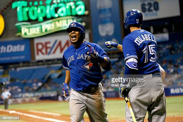 Edwin Encarnacion of the Toronto Blue Jays celebrates with teammate Chris Colabello after hitting a home run during the seventh inning of a game...