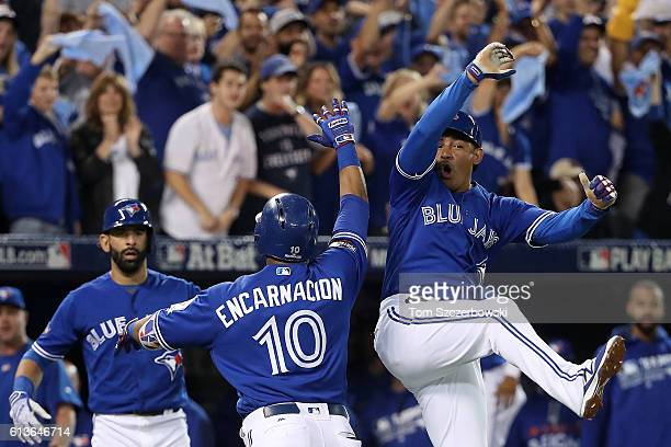 Edwin Encarnacion of the Toronto Blue Jays celebrates with teammate Ezequiel Carrera after hitting a two run home run in the first inning against the...