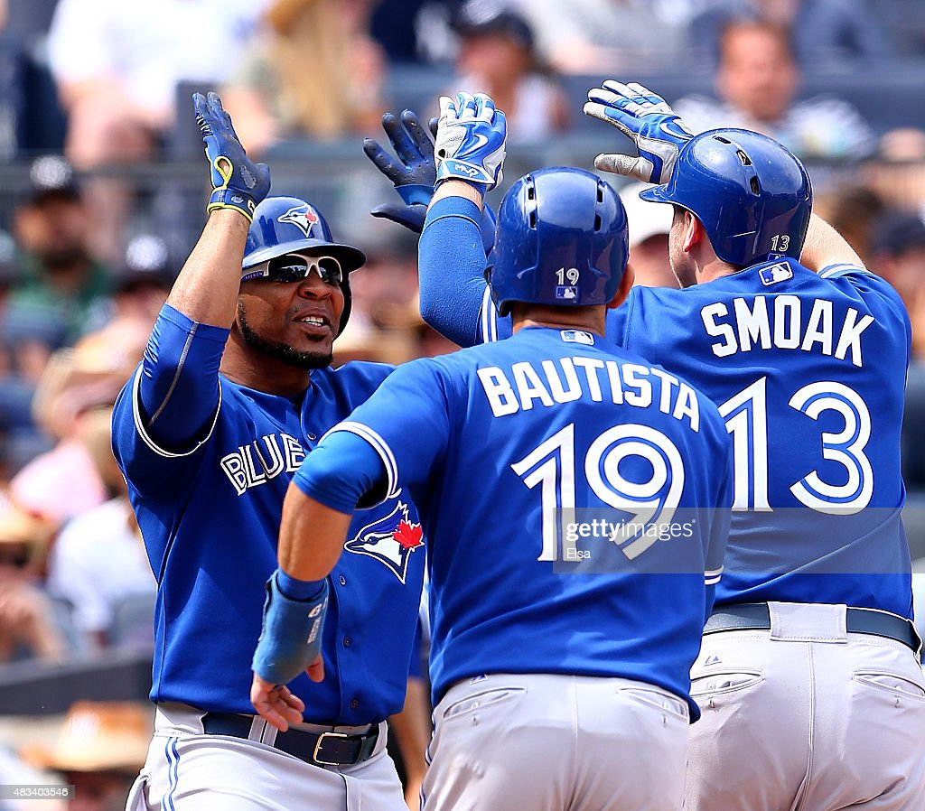 Edwin Encarnacion #10 of the Toronto Blue Jays celebrates with teammates Jose Bautista #19 and Justin Smoak #13 after Smoak hit a grand slam in the sixth inning against the New York Yankees on August 8, 2015 at Yankee Stadium in the Bronx borough of New York City.