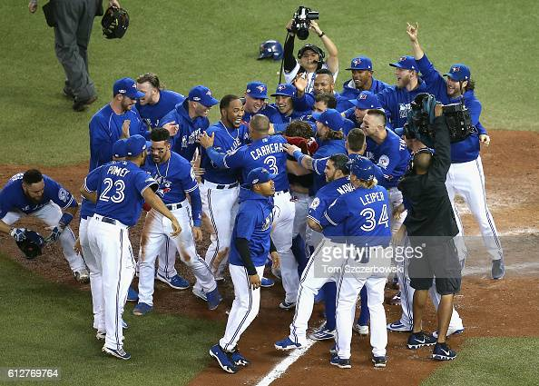 Edwin Encarnacion of the Toronto Blue Jays celebrates with teammates after hitting a threerun walkoff home run in the eleventh inning to defeat the...