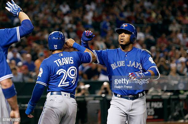 Edwin Encarnacion of the Toronto Blue Jays is congratulated by teammate Devon Travis after hitting a threerun home run against the Arizona...