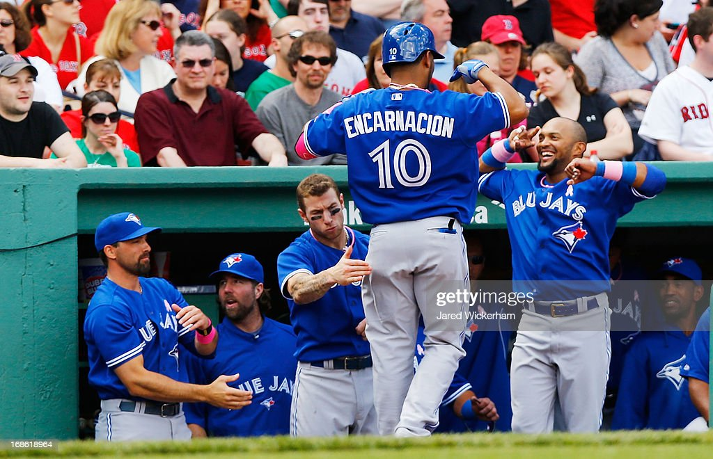 Edwin Encarnacion #10 of the Toronto Blue Jays is congratulated by teammates in the dugout after hitting a solo home run in the fifth inning against the Boston Red Sox during the game on May 12, 2013 at Fenway Park in Boston, Massachusetts.