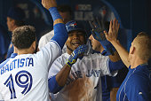 Edwin Encarnacion of the Toronto Blue Jays is congratulated by Jose Bautista and strength conditioning coach Chris Joyner after scoring a run in the...