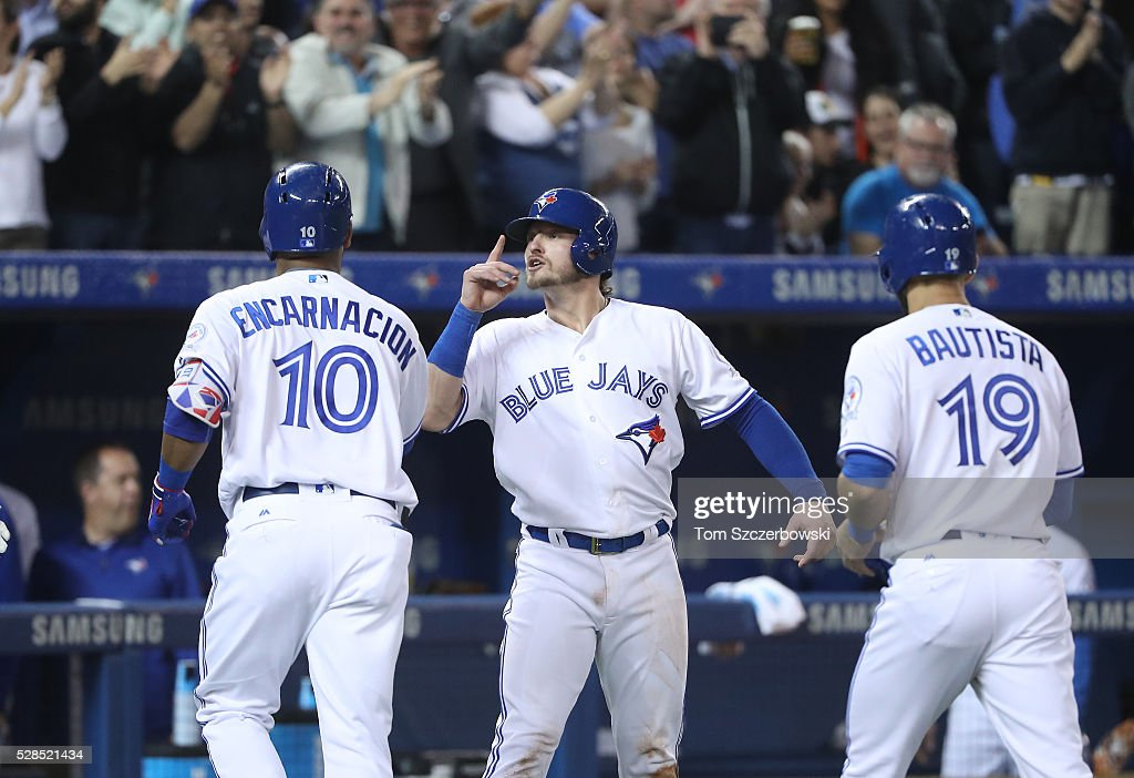 <a gi-track='captionPersonalityLinkClicked' href=/galleries/search?phrase=Edwin+Encarnacion&family=editorial&specificpeople=598285 ng-click='$event.stopPropagation()'>Edwin Encarnacion</a> #10 of the Toronto Blue Jays is congratulated by <a gi-track='captionPersonalityLinkClicked' href=/galleries/search?phrase=Josh+Donaldson&family=editorial&specificpeople=4959442 ng-click='$event.stopPropagation()'>Josh Donaldson</a> #20 and Jose Bautista #19 after hitting a three-run home run in the second inning during MLB game action against the Texas Rangers on May 5, 2016 at Rogers Centre in Toronto, Ontario, Canada.