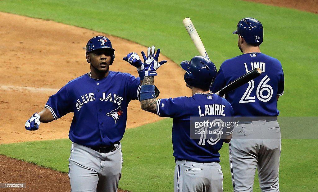 Edwin Encarnacion #10 (L) of the Toronto Blue Jays is greeted by Brett Lawrie #13 after Encarnacion hit a home run in the sixth inning against the Houston Astros at Minute Maid Park on August 24, 2013 in Houston, Texas.