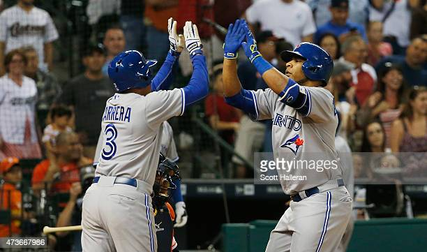 Edwin Encarnacion of the Toronto Blue Jays is greeted by teammate Ezequiel Carrera after hitting a tworun home run in the ninth inning during their...