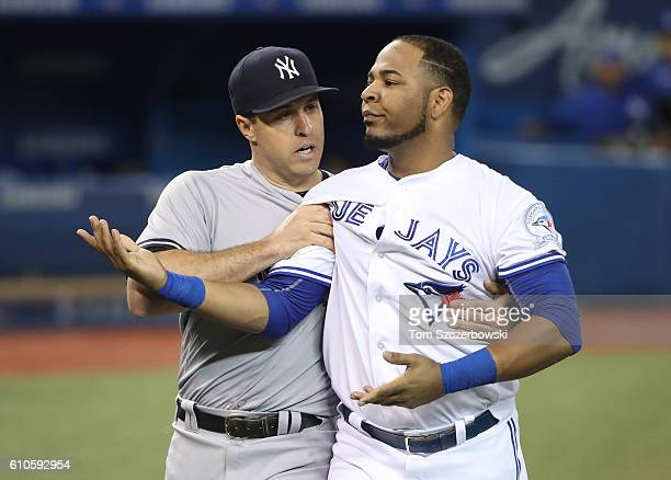 Edwin Encarnacion of the Toronto Blue Jays is restrained by Mark Teixeira of New York Yankees during a benchclearing incident in the second inning...