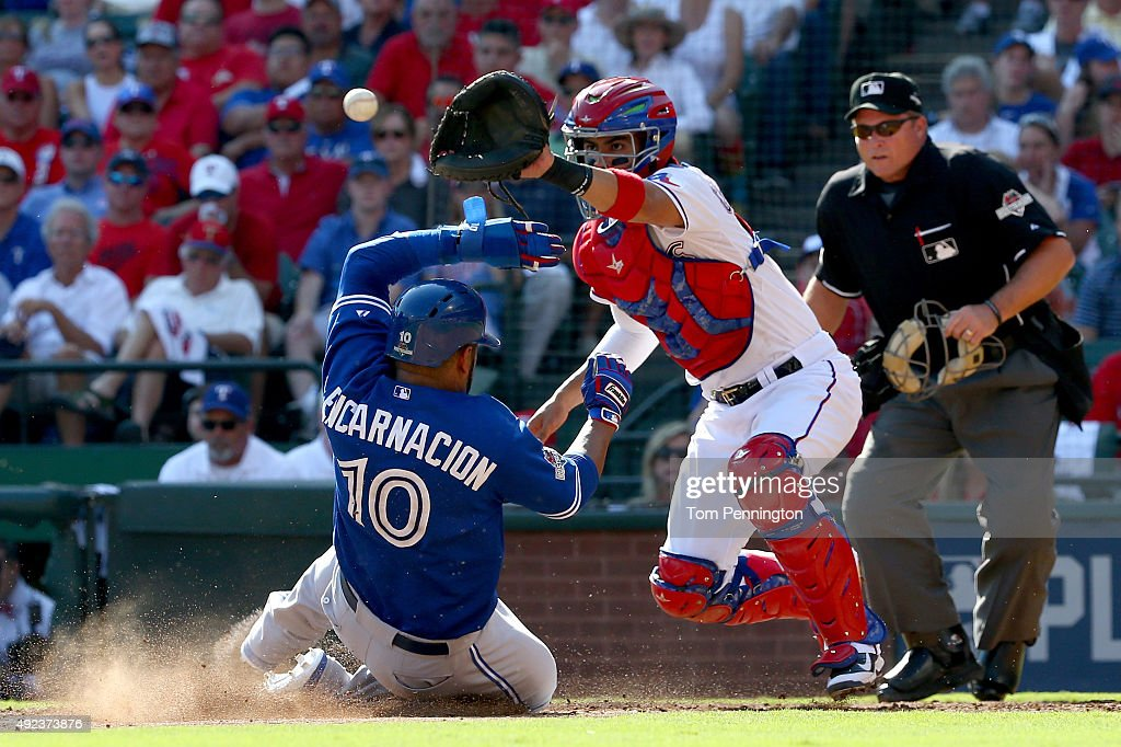 <a gi-track='captionPersonalityLinkClicked' href=/galleries/search?phrase=Edwin+Encarnacion&family=editorial&specificpeople=598285 ng-click='$event.stopPropagation()'>Edwin Encarnacion</a> #10 of the Toronto Blue Jays slides home safely before catcher <a gi-track='captionPersonalityLinkClicked' href=/galleries/search?phrase=Robinson+Chirinos&family=editorial&specificpeople=6809195 ng-click='$event.stopPropagation()'>Robinson Chirinos</a> #61 of the Texas Rangers in the third inning in game four of the American League Division Series at Globe Life Park in Arlington on October 12, 2015 in Arlington, Texas.
