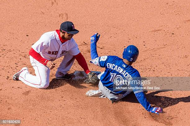 Edwin Encarnacion of the Toronto Blue Jays slides under the tag attempt of Marco Hernandez of the Boston Red Sox in the seventh inning on April 17...
