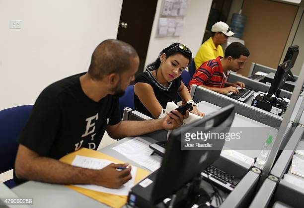 Edwin Medina and Coral Tapia use the resources availabe to look for work at an unemployment office a day after the governor gave a televised speech...