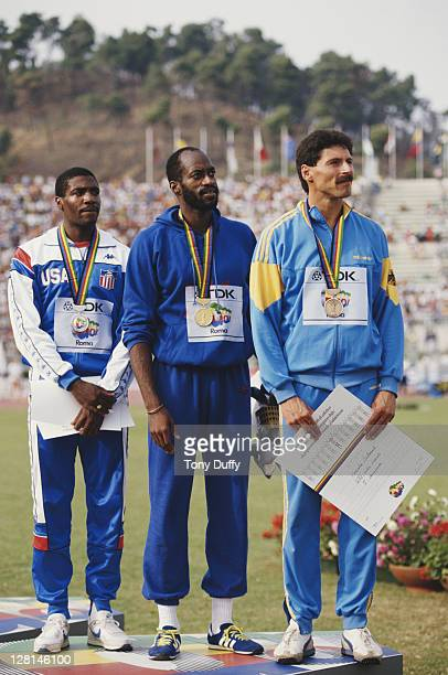 Edwin Moses of the United States with second place compatriot Danny Harris and third placed Harald Schmid of West Germany with their medals after the...