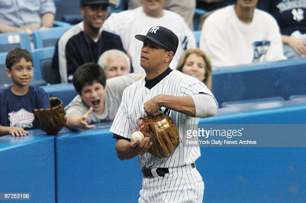 Edwin Schlossberg and wife Caroline Kennedy look on as their son John tries to get the attention of New York Yankees' Alex Rodriguez during warm ups...
